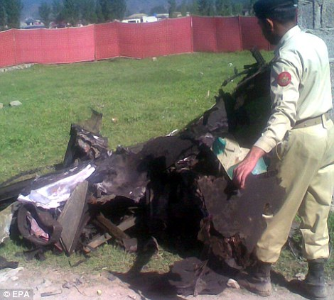 Crashed: A Pakistani Army soldier inspects the wreckage of the U.S. helicopter that crashed inside the compound after coming under fire. There were no casualties among the U.S. Navy Seals who mounted the attack on Bin Laden's compound