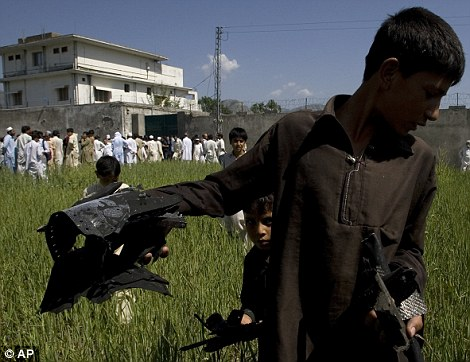 Souvenir: A Pakistani youngster carries metal pieces from the U.S. military helicopter that crashed outside Bin Laden's lair in Abbottabad