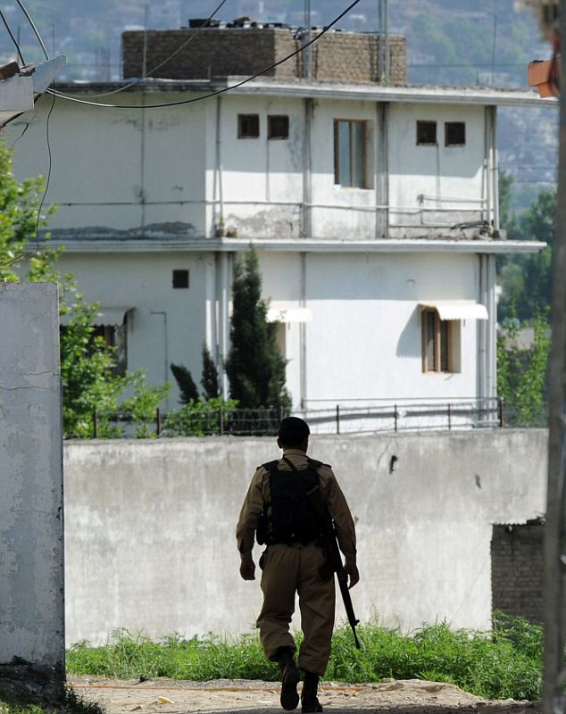 Treasure trove of intelligence: A Pakistani soldier walks toward the final hideout of Osama Bin Laden in Abbotabad, Pakistan, where SEALs recovered a mass of data