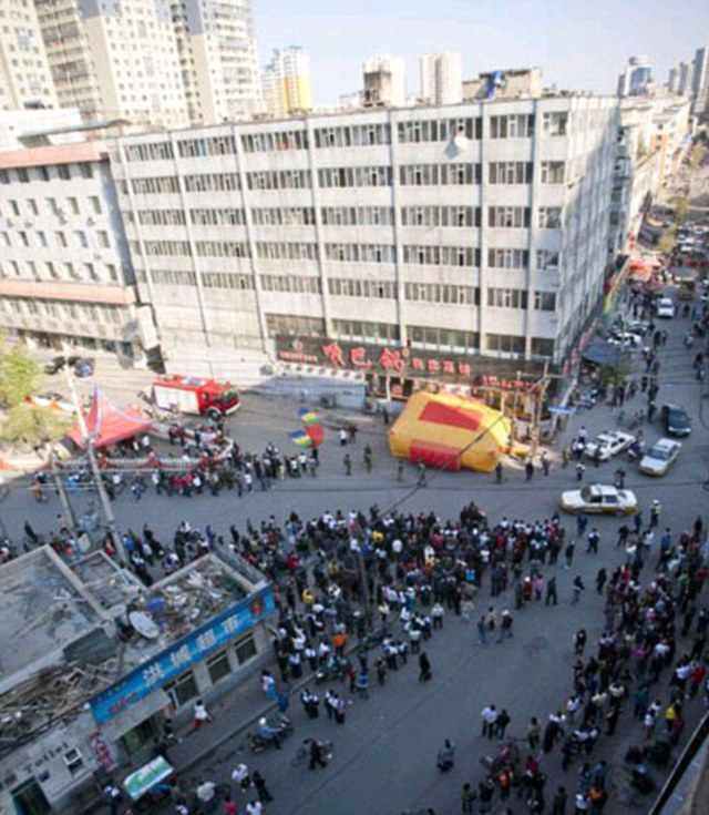 Dramatic: Hundreds gathered outside the residential building in Jilin province, north-east China to watch the amazing scenes unfold