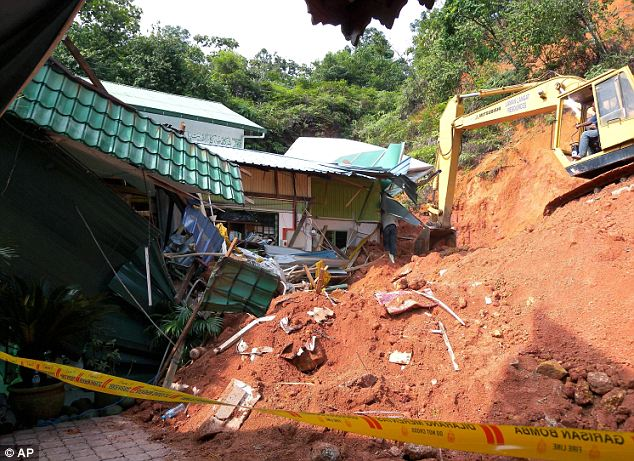 A rescuer uses a construction machine to search for the bodies believed to be buried by a landslide in Hulu Langat in central Selangor state, outside Kuala Lumpur, Malaysia