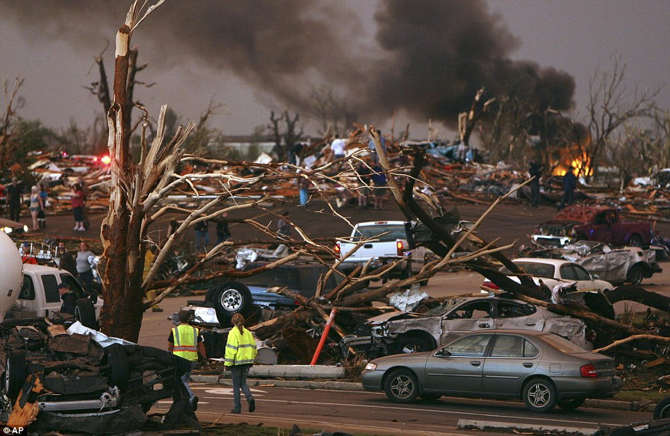 Devastation: Emergency personnel walk through a neighbourhood severely damaged by a tornado near the Joplin hospital. There are are no firm details on the number of dead or injured, as the hospital is out of action