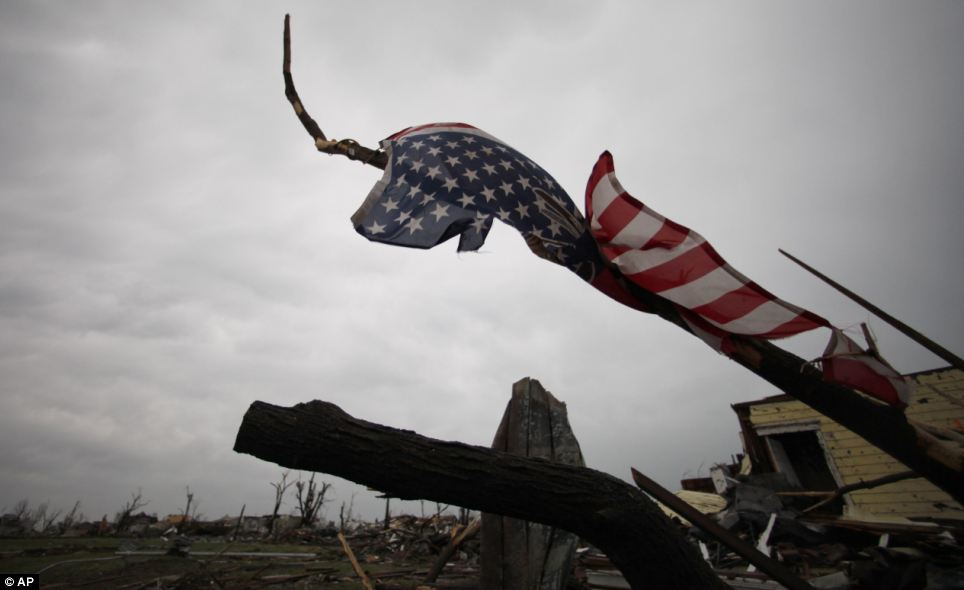 Somber: An American flag hangs from a twisted tree limb in Joplin