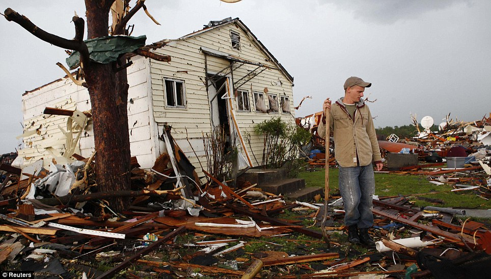 Little hope: Ryan Harper pauses in the shadow of a splintered tree as he searches for a missing friend after who may have been pulled away by the twister