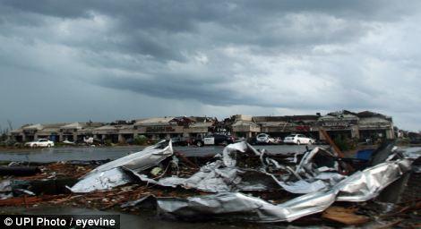 Gone: Dark skies threaten as the shopping centre sits destroyed in Joplin