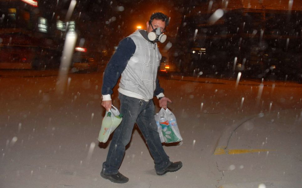 Protection: Carrying bottles of water and soft drinks this man wears a gas mask to avoid breathing in ash