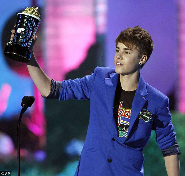 Happy: The teen scored the award for his role in Never Say Never - he appeared to have brand new ear piercings on both lobes