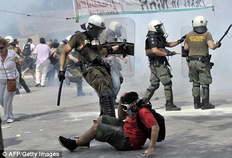 Kicked while he's down: A riot officer puts the boot into a protester during a demo in the centre of the Greek capital