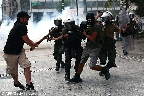 Riot: Protesters wielding weapons clash with riot police during the general strike against austerity plans that was held on Wednesday