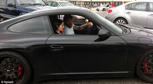 Sports car: Dunn pictured in his Porsche 911 GT3 with a female companion on June 12