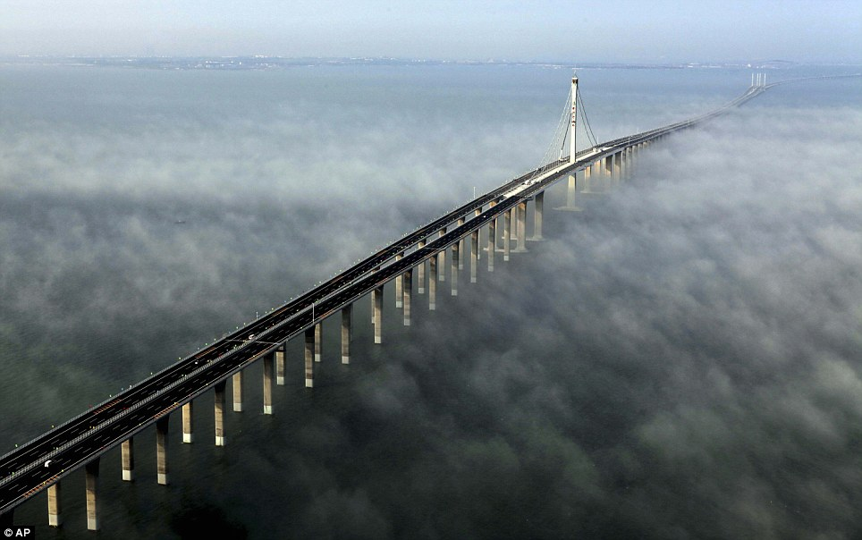 A bridge over misty waters: The immense £1billion structure which is supported by more than 5,000 pillars stretches for 24 miles along China's eastern port city of Qingdao to the offshore island Huangdao