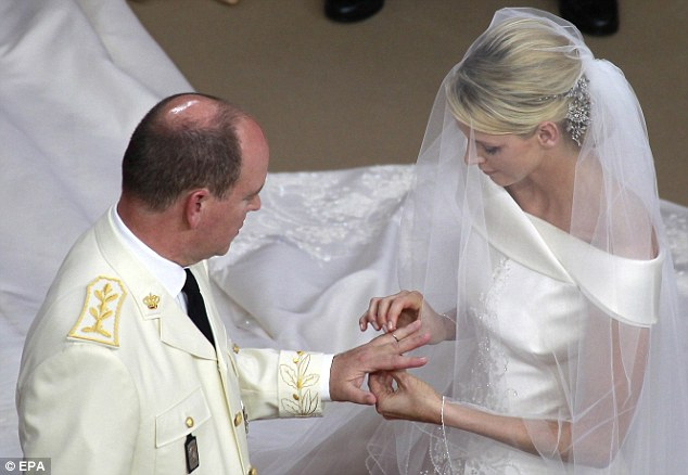 With this ring, I thee wed: Charlene places a 18-carat white gold platinum rings by Cartier on the Prince's finger