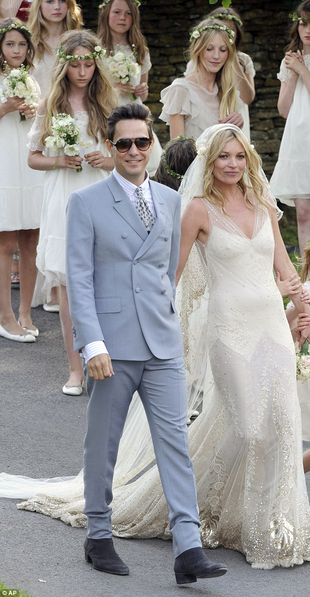 Presenting Mr and Mrs Rock 'N' Roll: The couple strides into the village after marrying in a Church of England ceremony