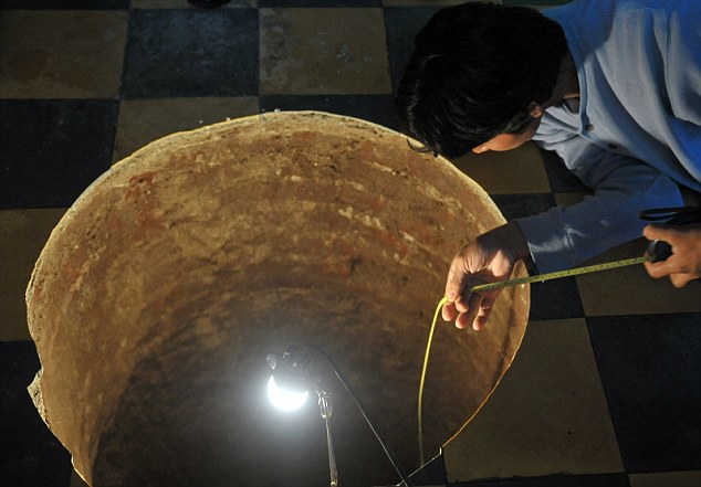 Inspection: A man measures the sinkhole as part of a team of officials from the country's natural disaster office and water utility company who visited the site