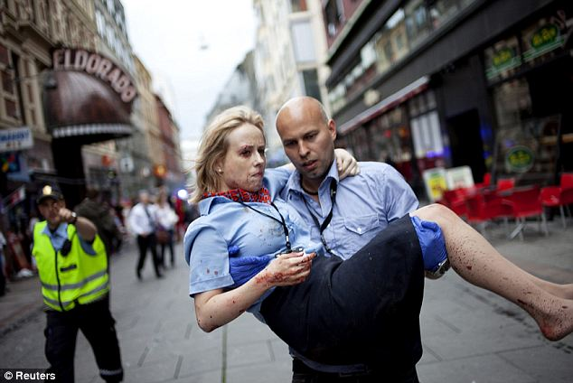 An injured woman is carried by a man at the site of the explosion that rocked the centre of Oslo