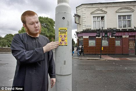 Drink outlawed: Uddin places his poster on a lamppost outside the now defunct Oliver Twist pub in a part of Leyton in London