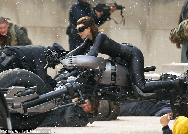 Heads down: Bodies fall to the floor as the stuntwoman whizzes around on the extraordinary vehicle