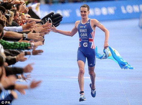 High-five: Alistair Brownlee greets the fans as he crosses the line to win