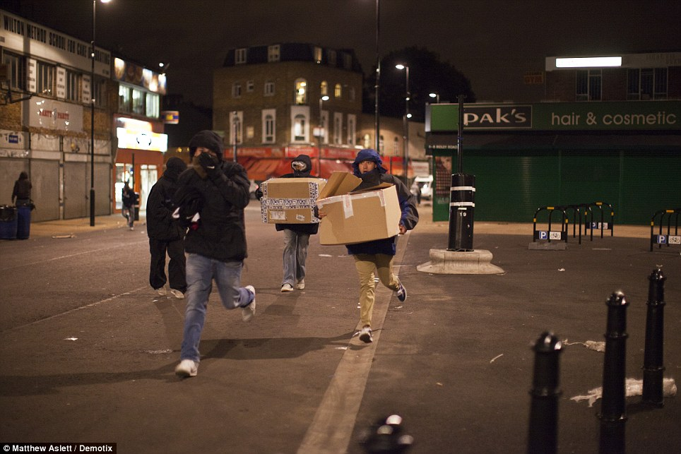 Dalston: Youths are seen running with boxes near near the area's Kingsland shopping centre