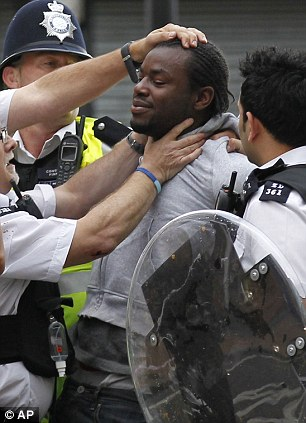 A suspected rioter is detained by police
