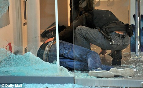 Undercover police officers arrest looters in the Swarovski Crystal shop in Manchester. One rioter lies injured and blood can be seen on the wall