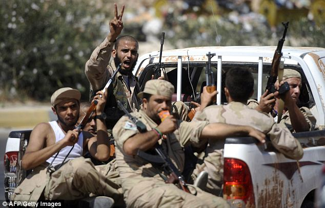 Armed to the teeth and baying for Gaddafi's blood: Rebels head towards the gates of Tripoli yesterday. They claimed the dictator had reached 'zero hour' for his reign of terror