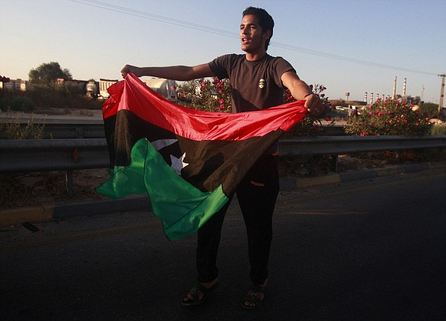 Freedom: A young man carries the flag of the Libyan republic along the streets of Maia