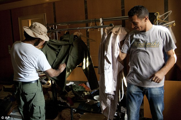 Try these for size: These two rebels examine clothes they want which belong to members of the dictator's family