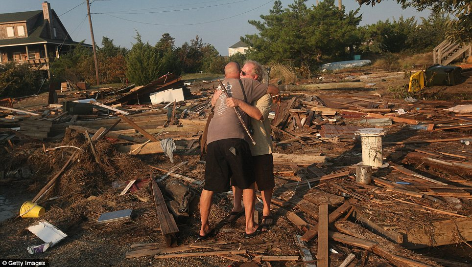 Picking up the pieces: A friend comforts Billy Stinson as the North Carolina man tries to salvage his belongings from the destroyed cottage