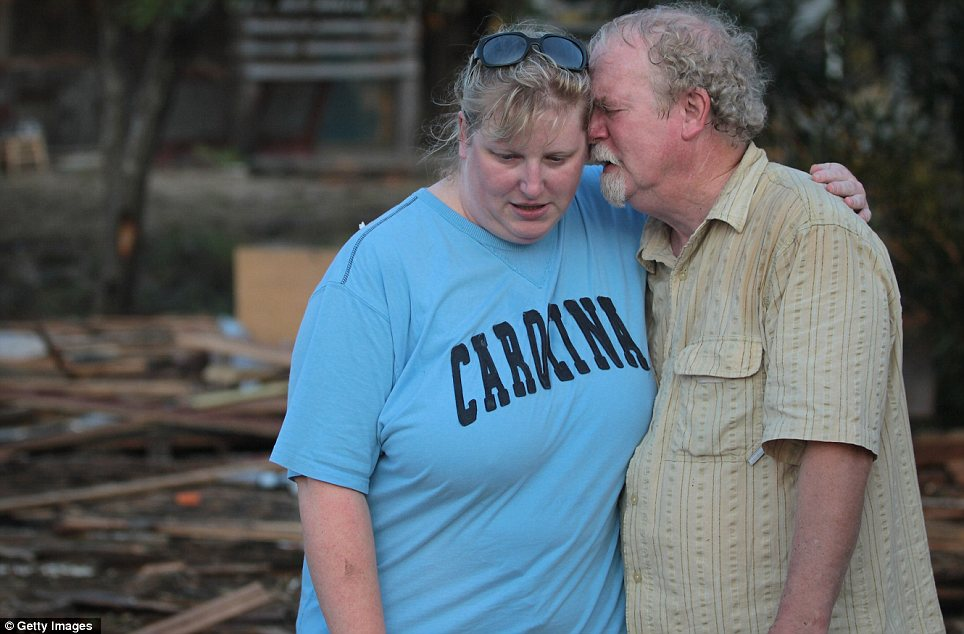 Grief: Billy Stinson, right, and his daughter Erin comfort each other as they stand next to the pile of debris that was once their cottage in Nags Head, North Carolina
