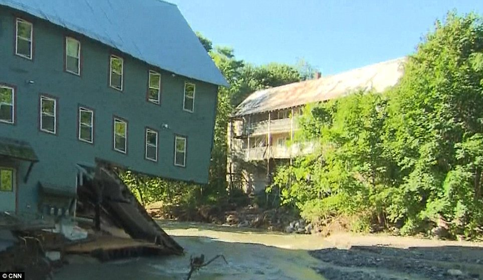 Devastation: A Vermont home is on the brink of collapse after it was nearly washed away by strong floodwaters
