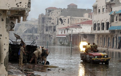 Waterlogged: Libyan rebel fighters fire at pro-Gaddafi forces as the battle for Sirte enters its final stages