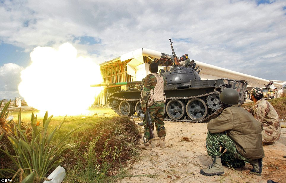 Attack: A tank of Libyan rebels fire at pro-Gaddafi fighters during the battle of Sirte
