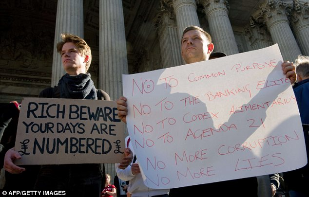 Protest: Demonstrators hold placards as they stand on the steps of St Paul's Cathedral