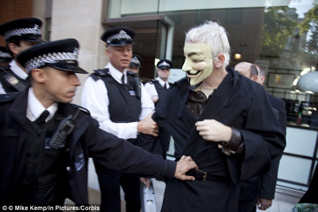 Wikileaks founder Julian Assange arrived at the protest wearing a mask, which he was promptly told to remove bv police