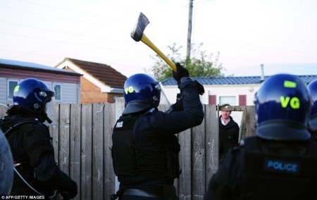 Police wield an axe as they attempt to enter Dale Farm