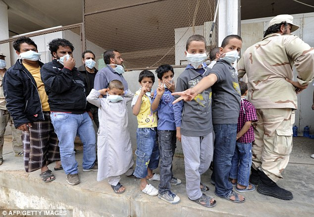 Public spectacle: Young children queue to see the body displayed in a meat locker in Misrata
