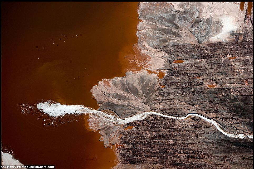 A river bleached white with the waste of aluminium production snakes through the parched Louisiana landscape before emerging into a muddy red lake in Darrow where the colours swirl together as on a palette