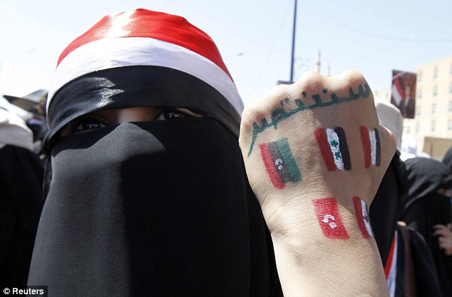 Making a fist of it: An anti-government protester displays paintings on her hand of flags of other countries involved in the Arab Spring
