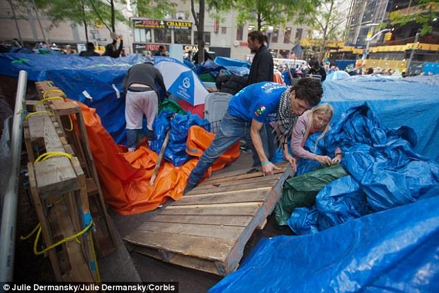 De larga distancia: Zuni Tikka, de 37 años ayuda a fortalecer su tienda de campaña en Zuccotti Park como el clima húmedo y frío se mueve in Ella ha sido parte de ocupar Wall Street desde el día en que comenzó el 17 de septiembre
