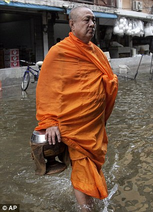 A Thai Buddhist monk wades through floodwaters in Bangkok,