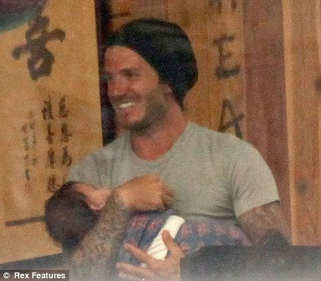 Happy as Larry: David Beckham smiles while looking after daughter Harper as his sons take part in a karate class in Los Angeles