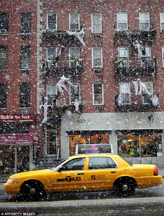 Ghoulish: A taxi drives past a Halloween-decorated house as snow falls in New York today