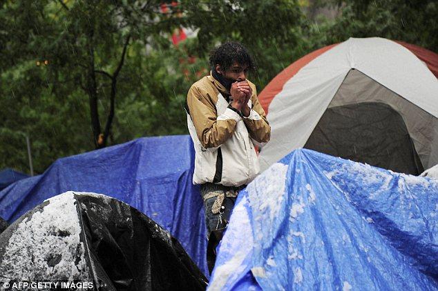 Lucha: Una Ocupar la calle Muro de manifestante intenta entrar en calor cuando se despierta entre la nieve salpicada de tiendas de campaña