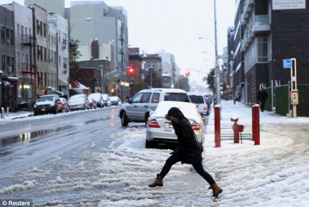 Salto: Una mujer trata de saltar sobre un charco durante una tormenta de nieve temprano en Nueva York