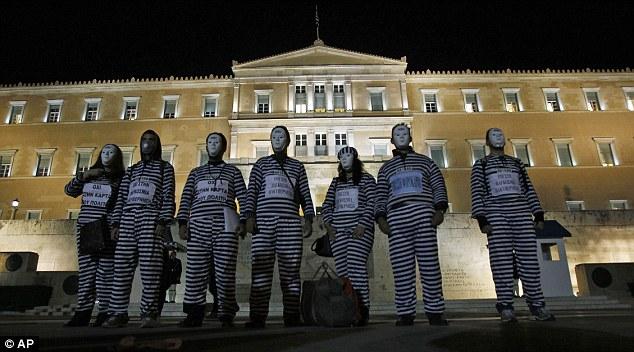 La furia del pueblo: Los manifestantes se manifiestan contra las medidas de austeridad previsto ante el Parlamento griego ayer por la noche como primer ministro del país, obtuvo el respaldo de un referéndum sobre el rescate de acuerdo