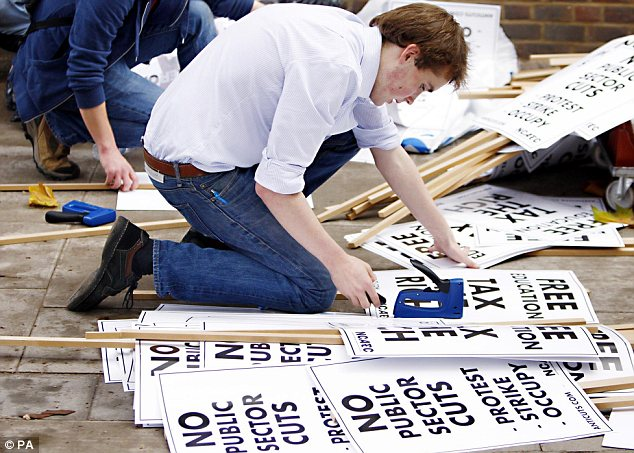 Preparation: An organiser puts placards together ahead of today's student demonstration