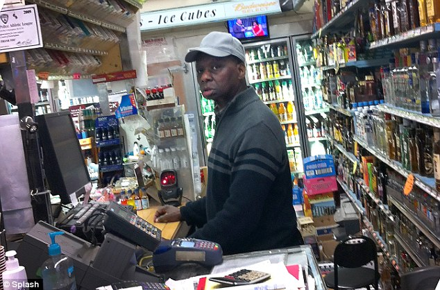Day job: Onyango Obama, who faced drink-driving charges today, is seen working behind the till at Conti Liquors in his home town of Framingham, Massachusetts