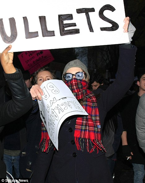 Anarchy queen: Anne covers her face in her scarf as night falls on New York