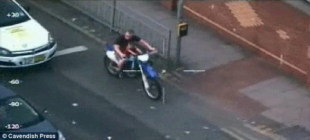 Feckless: Ryan Ward drives off into the traffic with his young son, wearing neither helmet nor protective clothing
